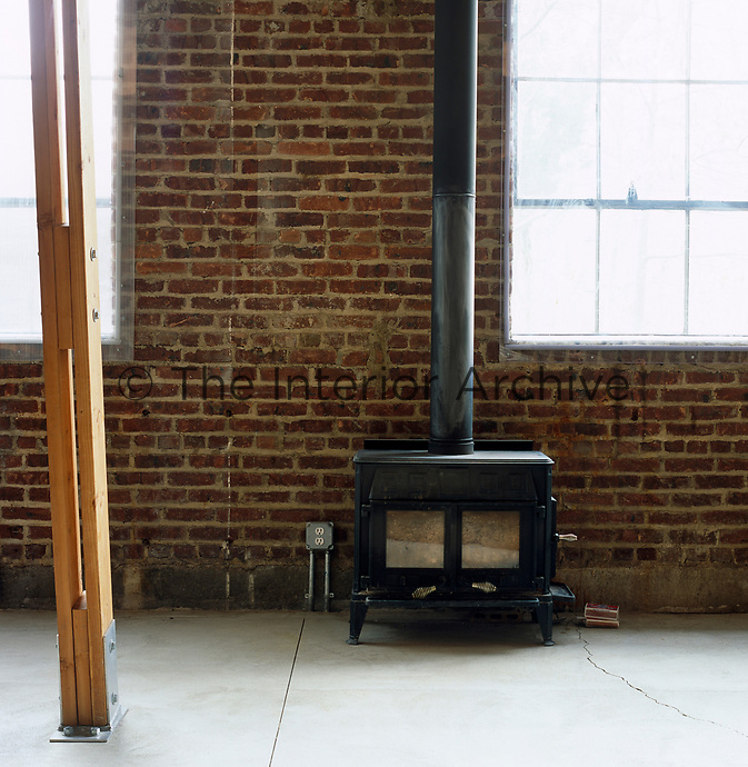 A wood-burning stove against an exposed brick wall reveals the raw structure of the original factory building