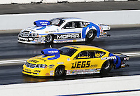 Feb. 16, 2013; Pomona, CA, USA; NHRA pro stock drover Jeg Coughlin Jr (near) races alongside Allen Johnson during qualifying for the Winternationals at Auto Club Raceway at Pomona.. Mandatory Credit: Mark J. Rebilas-