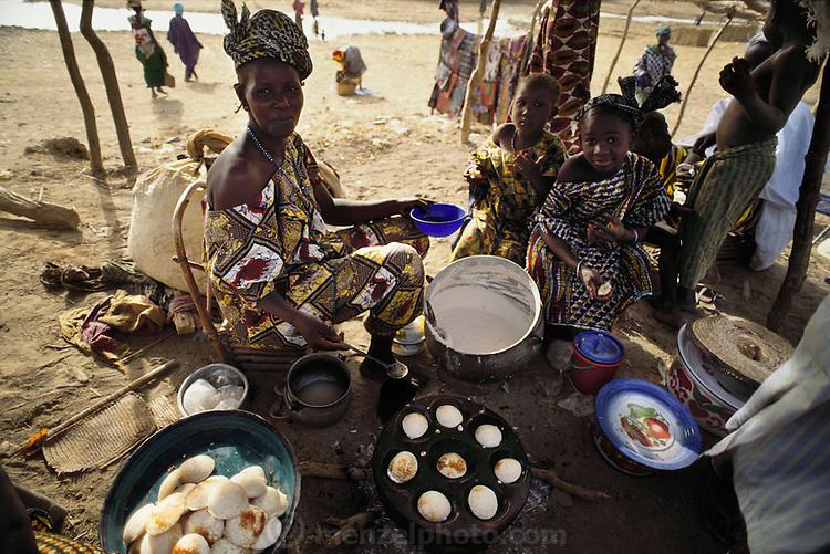 "A villager makes fried grain cakes called ""ngome"" to sell at the Sunday market in Kouakourou, Mali. Kouakourou is the home village of the Natomo family lives in two mud brick houses near the banks of the Niger River. Material World Project."