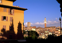 Italy, Siena, Tuscany, elderly couple at window with view of Siena skyline