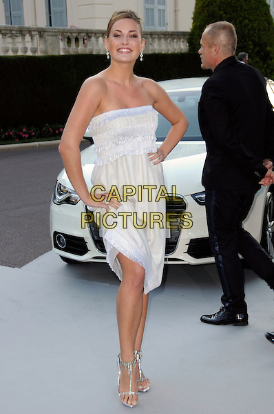 GUEST .arrivals at amfAR's Cinema Against AIDS 2010 benefit gala at the Hotel du Cap, Antibes, Cannes, France during the Cannes Film Festival.20th May 2010.amfar full length white cream pale yellow strapless dress hand on hip .CAP/CAS.©Bob Cass/Capital Pictures.