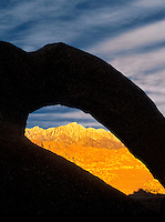 Lone Pine Peak as seen through silhouetted arch. Alabama Hills, California.