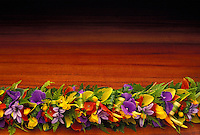 Colorful haku flower lei on koa wood backround