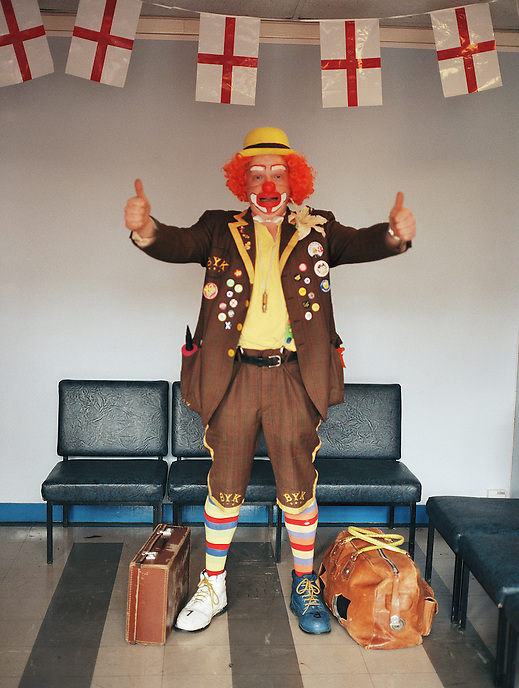HATTERSLEY, UK - BaldyTruk, a local clown from the neighbouring town of Hyde, poses for a portrait in the lobby of the local community centre.. .The Hattersley Estate was created in the early 1960s to house residents displaced by the slum clearances of inner city Salford and Manchester and soon gained notoreity between 1963 and 1965 as the home to the Moors Murderers, Myra Hindley and Ian Brady. Lying in a relatively isolated area on the edge of the Pennines, residents today continue to wait for the investment and infrastructure promised to them decades ago. In the gap between promise and reality, a unique characted formed during years of adversity continues to thrive on the estate.