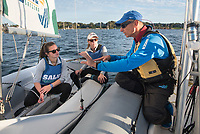 John Ingals, Salve Regina University Sailing Team Head Coach works with Skipper Jen Killian,'19, center, and Crew Madeline Lark '20 , as the team practices in the Newport Harbor.