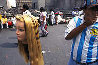 A street salesman demonstrates his hair clips using the head of a manequin in front of the Templo Mayor in mexico city´s center.