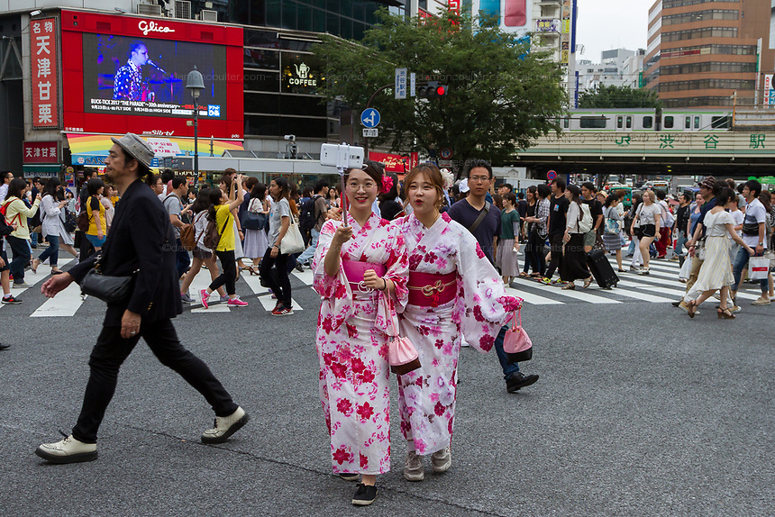 Two Asian women tourists, dressed in pink kimono, pause for a selfie in the middle of Shibuya Crossing, Shibuya, Tokyo, Japan Tuesday June 27th 2017