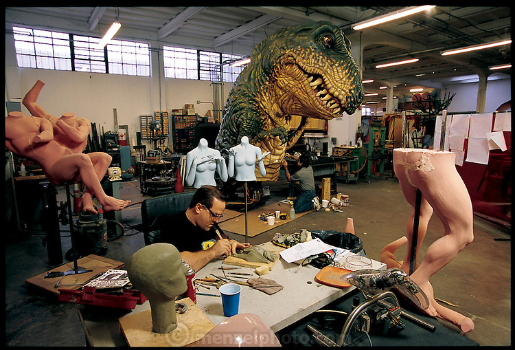 Oblivious of the seeming threat from Tyrannosaurus Rex, staff artist Lance Jacobson sculpts a batlike creature in one of the Sally Company's large, eclectic workspaces. The bat is destined for an interactive amusement park ride in Terra Mítica, a new Spanish theme park. In the ride, patrons will sit in automated, chariot-like vehicles that rattle through a mythical Greek kingdom. Armed with low-intensity, laser-firing crossbow pistols, they will take potshots at dozens of animatronic evil doers and monsters, among them, the bat-thing Jacobson is working on today. Jacksonville, Florida. From the book Robo sapiens: Evolution of a New Species, page 210-211.