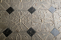 A detail of the shell-inlaid black and white floor of the folly that features various motifs