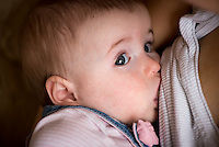 "A close-up of a nine month old baby girl breastfeeding.<br /> <br /> Image from the breastfeeding collection of the ""We Do It In Public"" documentary photography picture library project: <br />  www.breastfeedinginpublic.co.uk<br /> <br /> <br /> Dorset, England, UK<br /> 08/03/2013<br /> <br /> © Paul Carter / wdiip.co.uk"