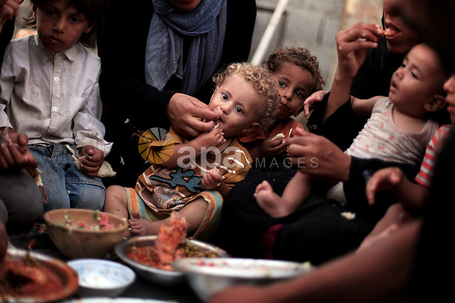 A Palestinian refugee family break their fasting at their home in one of the poorest regions at al-Zaitoon neighborhood, during the Holy month of Ramadan, in Gaza city, 26 July 2013. Muslims throughout the world are celebrating the fasting month of Ramadan, the holiest month in the Islamic calendar, refraining from eating, drinking, smoking and sexual activities from dawn to dusk. Photo by Ali Jadallah