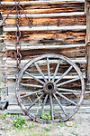 An old wagon wheel leans against an old log cabin.