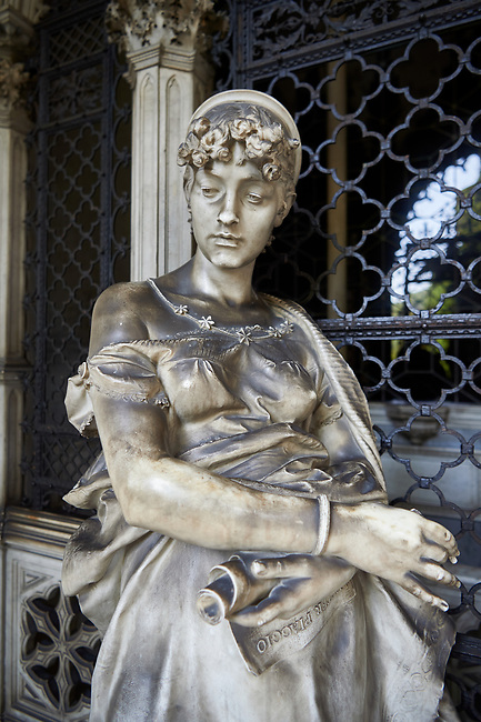 Picture and image of the stone sculpture of a young women waiting by the gates of the tomb in a Borgeois Realistic style. The Piaggio Family Tomb sculpted by G Scanzi 1885. Section D no 36, the monumental tombs of the Staglieno Monumental Cemetery, Genoa, Italy