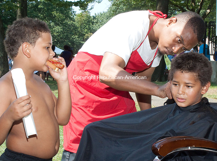 WATERBURY CT.-21 AUGUST 2013 081413DA05- Hair Stylist of Butterfly Affects in Waterbury, Chris Jowers gives a free hair cut to Freddie Jones, 8, of Waterbury as his brother Michael, 7, looks on eating his  Frankie's Hot Dog during the 'It's a Beautiful Day' theme Annual City-wide Back to School Rally celebrating the start of the new Waterbury school year that begins on August 27. The event was held at Library Park in Waterbury on Wednesday and offered information regarding after-school programs, healthcare support and community resources. They also offered school supplies, games, food, entertainment by David Green and local youth and a live broadcast by Big J from HOT 93.7 and free haircuts. Waterbury Youth Service System, Inc., along with the Mayor's office, the Department of Education, and other local organizations, coordinate and host the rally which was free and open to all Waterbury school children and their families.children and their families.<br /> Darlene Douty Republican American