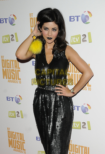 MARINA DIAMANDIS of Marina and the Diamonds .At the BT Digital Music Awards 2010,.the Roundhouse, Camden, London, England, UK, September 30th 2010..half length black sequined sequin hand on hip belt wrist watch dress dark lipstick sleeveless make-up yellow fluffy ball pompom wristlet .CAP/CAN.©Can Nguyen/Capital Pictures.