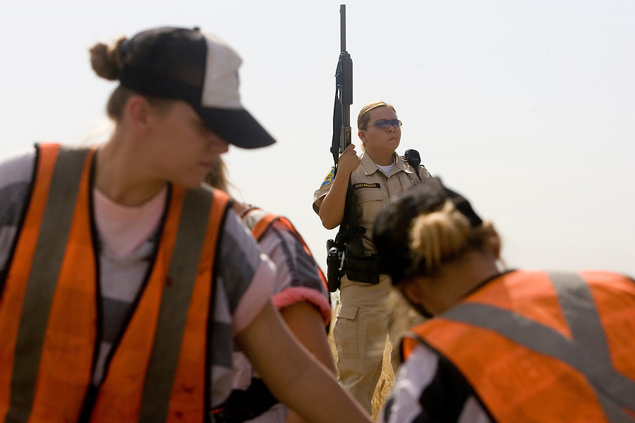 5/16/07- 144418- Detention officer Lorena Bustamante watches over the chain gang as they work in Glendale. . (Pat Shannahan/ The Arizona Republic)