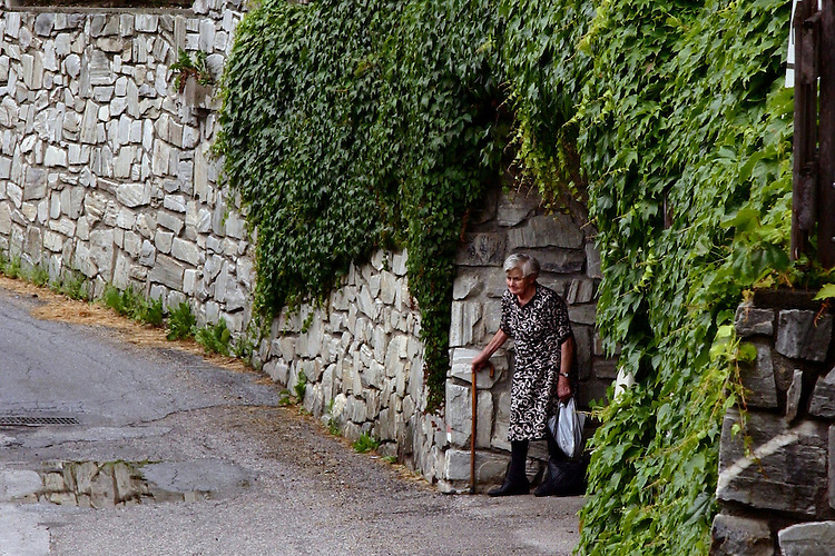 An old woman waits for the bus in a small town in the Italian Alps.