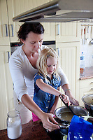 Polish mom helping daughter age 4 cook stir at stove. Zawady Central Poland