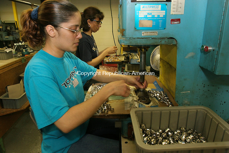 CHESHIRE, CT-28 June 2005-062805TK07 Lisa Rivera of Waterbury working a multipress hand assembly operation on buttons that are destined for use on military uniforms at the Army's West Point Military Academy.  Tom Kabelka staff photo (Lisa Rivera, West Point Military Academy)CQ