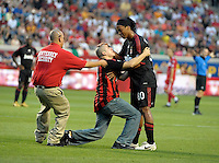 An AC Milan fan who ran out on the field gets a pat on the head from AC Milan midfielder Ronaldinho (80).  AC Milan defeated the Chicago Fire 1-0 at Toyota Park in Bridgeview, IL on May 30, 2010.