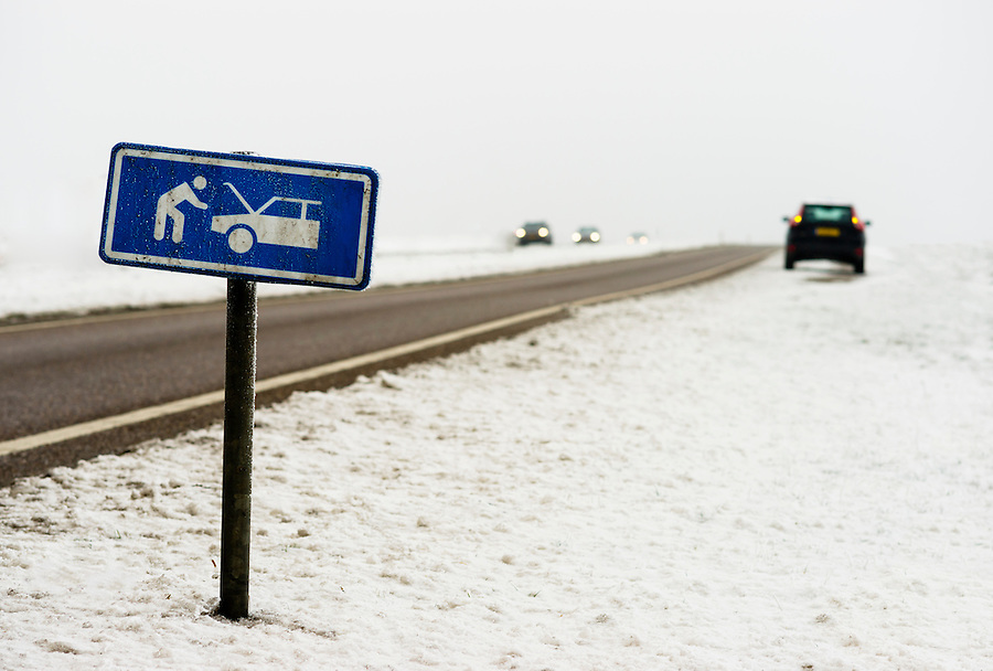 A car with a breakdown alongside the winter road