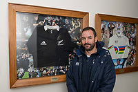 Otago Boys' High School First XV coach Ryan Martin stands next to Richie McCaw's All Blacks jersey which is displayed at the school in Dunedin, New Zealand on Friday 22 June 2018.  Photo: Adam Binns / lintottphoto.co.nz