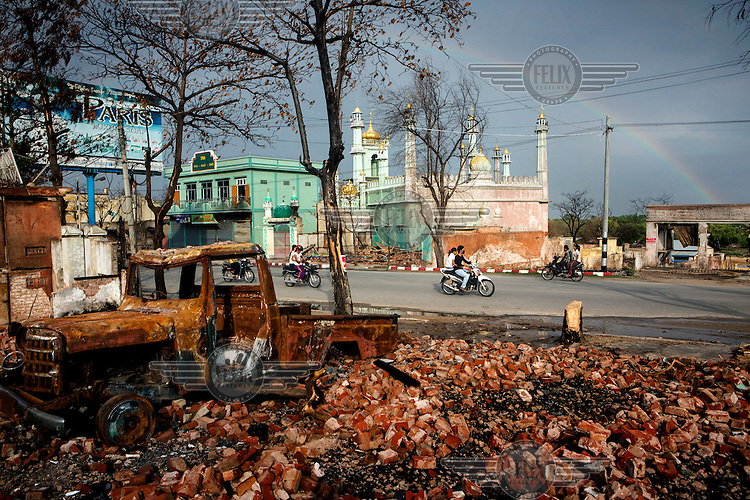 People drive past a burned out vehicle, damaged buildings and mosque, that was also damaged, in the Mingalar Zayyone Muslim quarter, that was razed by Buddhists in ethnic violence in March, in Meikhtila, Myanmar (Burma) on May 23, 2013. The now destroyed Mingalar Zayyone Madrassa where Abdul Razak, 15 (also called Ye Myin) was killed. In the four days of ethnic violence starting on March 21st, 2013 over 43 people were killed in Meikhtila and nearly 13,000 people, mostly Muslims, were driven from their homes and businesses. /Felix Features