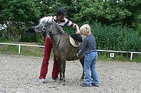 Shetland-Pony, Shetlandpony, Shetty, Shetti, Ponyhof, Shetland - Pony wird eingeritten, Ponyhof, Reiten, Kind und Reitlehrerin satteln auf
