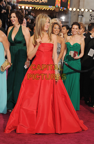 Jennifer Aniston (wearing Valentino).85th Annual Academy Awards held at the Dolby Theatre at Hollywood & Highland Center, Hollywood, California, USA..February 24th, 2013.oscars full length red strapless dress gown gold clutch bag hand arm.CAP/ROT/TM.©Tony Michaels/Roth Stock/Capital Pictures