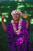 Hula teacher dancing with pink plumeria leis