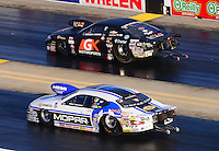 Sept. 14, 2012; Concord, NC, USA: NHRA pro stock driver Allen Johnson (near lane) races alongside Erica Enders during qualifying for the O'Reilly Auto Parts Nationals at zMax Dragway. Mandatory Credit: Mark J. Rebilas-