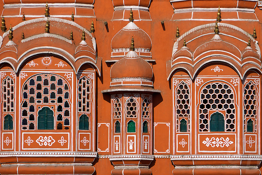 Renowned as the 'Palace Of The Winds', or Hawa Mahal, is one of the prominent attractions in Jaipur city. Located in the heart of Jaipur, this beautiful five-storey palace was constructed in 1799 by Maharaja Sawai Pratap Singh who belonged to Kachhwaha Rajput dynasty. The main architect of this palace built of red and pink sandstone, is Lal Chand Ustad and the palace is believed to have been constructed in the form of the crown of Krishna, the Hindu god. Considered as an embodiment of Rajputana architecture, the main highlight of Hawa Mahal is its pyramid shape and its 953 windows or 'Jharokhas' which are decorated with intricate designs. The main intention behind the construction of the Mahal was to facilitate the royal women and provide them a view of everyday life through the windows, as they never appeared in public. Read further to know more about Hawa Mahal, its history, architecture and its visiting hours.