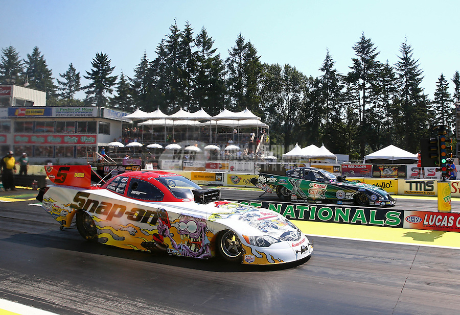 Aug. 3, 2014; Kent, WA, USA; NHRA funny car driver Cruz Pedregon (near) races alongside John Force during the Northwest Nationals at Pacific Raceways. Mandatory Credit: Mark J. Rebilas-USA TODAY Sports