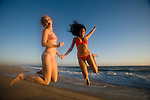 Happy girl friends jump for joy at beach in California, USA at sunset, dusk, CA, america