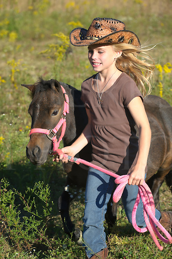 Girl running miniature horse through summer goldenrod field in late afternoon, young blonde with cowboy hat, Pennsylvania, PA, USA.