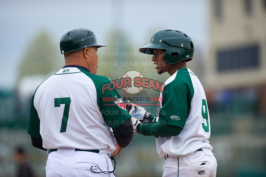 Fort Wayne TinCaps Xavier Edwards (9) talks to fielding coach Jhonny Carvajal (7) after reaching first base during a Midwest League game against the Kane County Cougars at Parkview Field on May 1, 2019 in Fort Wayne, Indiana. Fort Wayne defeated Kane County 10-4. (Zachary Lucy/Four Seam Images)