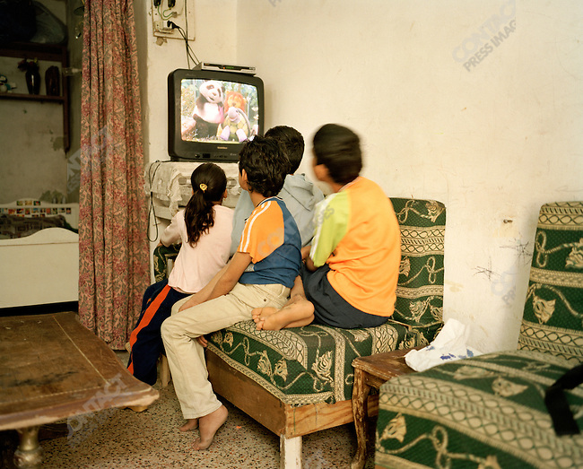 Iraqi refugee children watching TV in the two-room apartment where they live with their mother, Fatin and father, Samir. The children are unable to attend school. They are Sabian Mandaean, a minority group in Iraq who have suffered extreme cases of persecution. There are 19 family members living in the Hashmi Al Shemali area of Amman, Jordan. April, 2007.