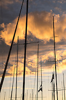 Sailboat masts silhouetted against sunset.