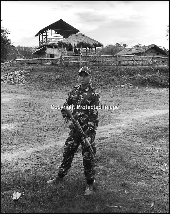 25 year old Lance Corporal Desring Dimasa a.k.a 'The Undertaker' poses for a portrait with an AK 56 assault rifle at the Basabari camp of the ceasefire terrorist group Dima Halim Daoga (DHD) in Mibang in North Cachar hills of Assam, India.