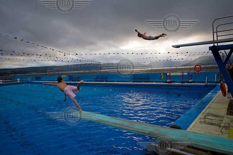 Children dive into Gourock outdoor swimming pool beside the Clyde estuary, near Glasgow..
