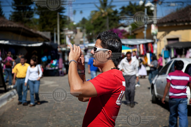 An El Salvadorean tourist takes a picture. Despite low average incomes, since the end of the country's civil war in 1992, Salvadorians have increasingly toured their own country on holidays.