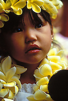 Portrait of young Asian local girl (3-4) with yellow plumeria leis