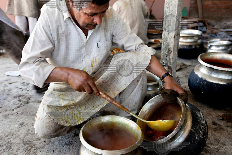 A Waza, or cook in the Kashmiri food tradition, stirs a dish while preparing for a Wazwan feast, a multi-course banquet that is traditional in Kashmir. /Felix Features