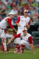 North Carolina State pitcher Carlos Rodon (16) falls to the ground avoiding catcher Brett Austin (11) as he makes a throw to first base while third baseman Grant Clyde (22) watches during Game 10 of the 2013 Men's College World Series against the North Carolina Tar Heels on June 20, 2013 at TD Ameritrade Park in Omaha, Nebraska. The Tar Heels defeated the Wolfpack 7-0, eliminating North Carolina State from the tournament. (Andrew Woolley/Four Seam Images)