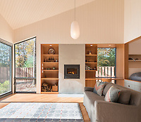 A light and airy modern living room with panelled walls and ceiling. A wood burning stove is set into a chimney breast, which is flanked by built-in wood shelves.