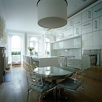 This contemporary white kitchen/dining room features mirrored cupboards with integrated appliances