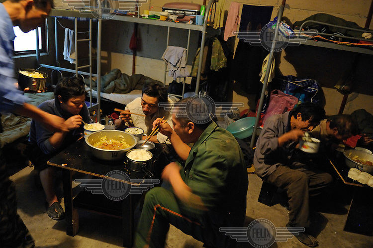 Lunch break for migrants in their temporary dormitory block. They live twelve to the room in bunk beds, while working on a major construction site in the Central Business District.