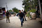A foreign photojournalist runs for cover while Kashmiri demonstrators raise anti-India slogans, throw stones and clash with Indian police during an anti-election protest in downtown Srinagar, summer capital of Jammu and Kashmir, India. A 50 hour curfew was imposed on May 5th to boycott the elections on May 7, 2009. ..Kashmir went into polls on the 4th round of Indian general elections. About 26 percent polling was recorded in the Indian parliamentary elections held in Kashmir on Thursday, May 7th 2009. The poll percentage was on the higher side this year as compared to 2004 polls when 15.04 percent polling was recorded.