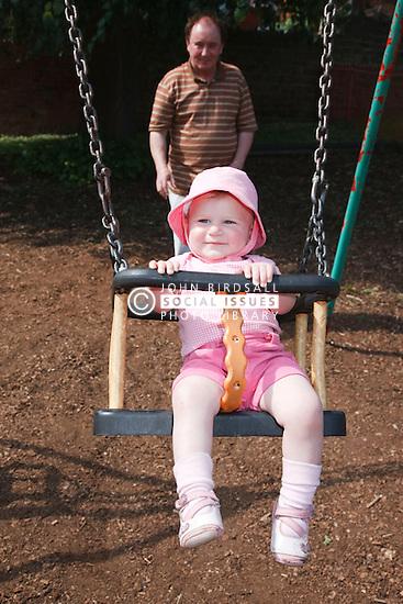 Grandfather pushing baby on swing