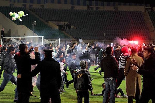 POR05.PORT SAID (EGIPTO).1/2/2012.-La policía observa desde el cesped mientras aficionados egipcios se enfrentan en las gradas del estadio de Port Said, Egipto, hoy miércoles 1 de febrero de 2012. Al menos 73 personas han muerto y 136 han resultado heridos han resultado heridas por los enfrentamientos entre las hinchadas de dos equipos de fútbol egipcios en Port Said (noreste), según informó a Efe el delegado de Sanidad de la ciudad, Helmy Ali al Atny.Al Atnye explicó que la mayoría de fallecidos perdieron la vida por fracturas en el rostro y por hemorragias internas, y también hubo un gran número de ingresados por caídas desde los graderíos del estadio, donde se enfrentaban el Al Ahli, de El Cairo, y el equipo local, Al Masri.EFE/STRINGER